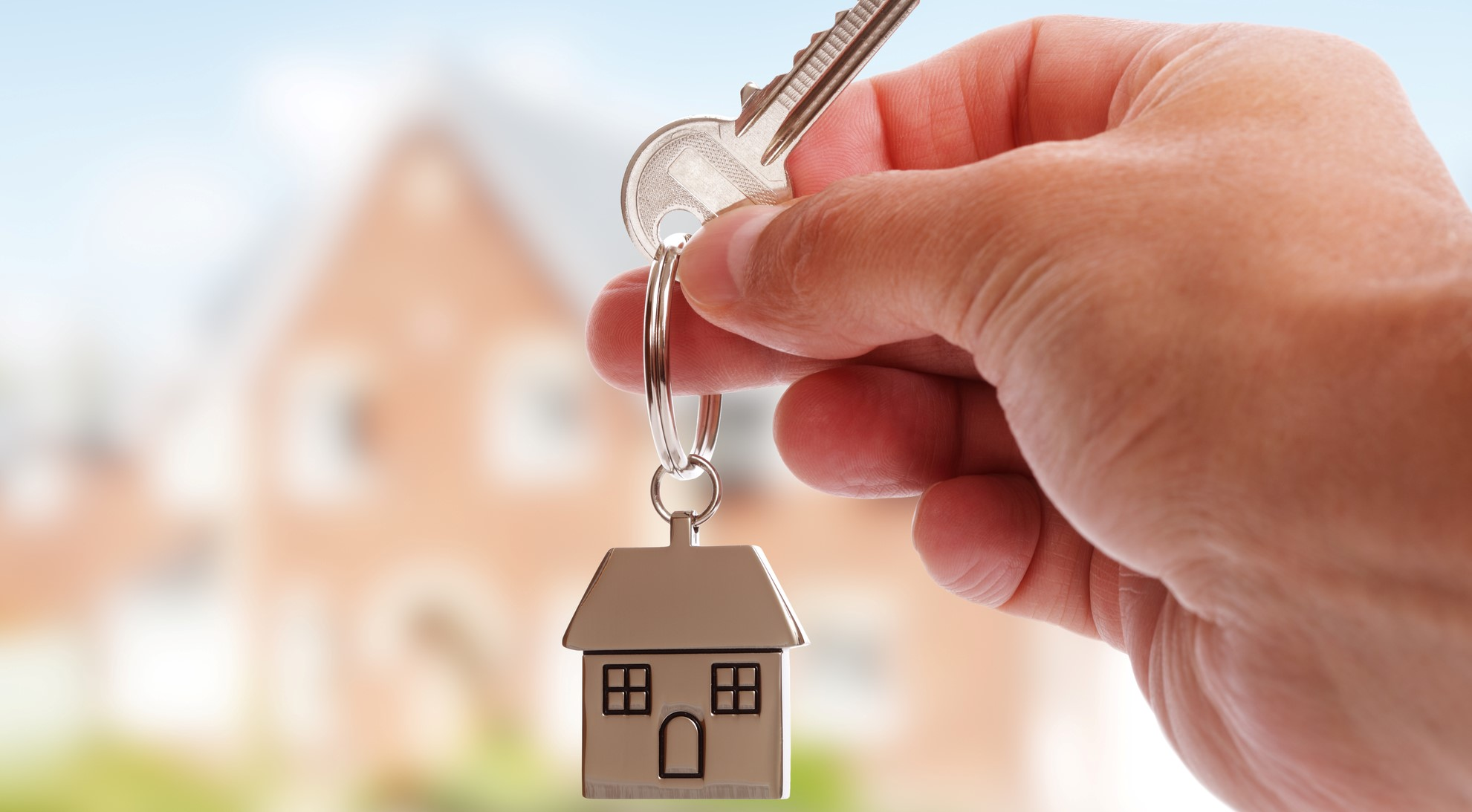 Image of person holding a keyring in the shape of a house