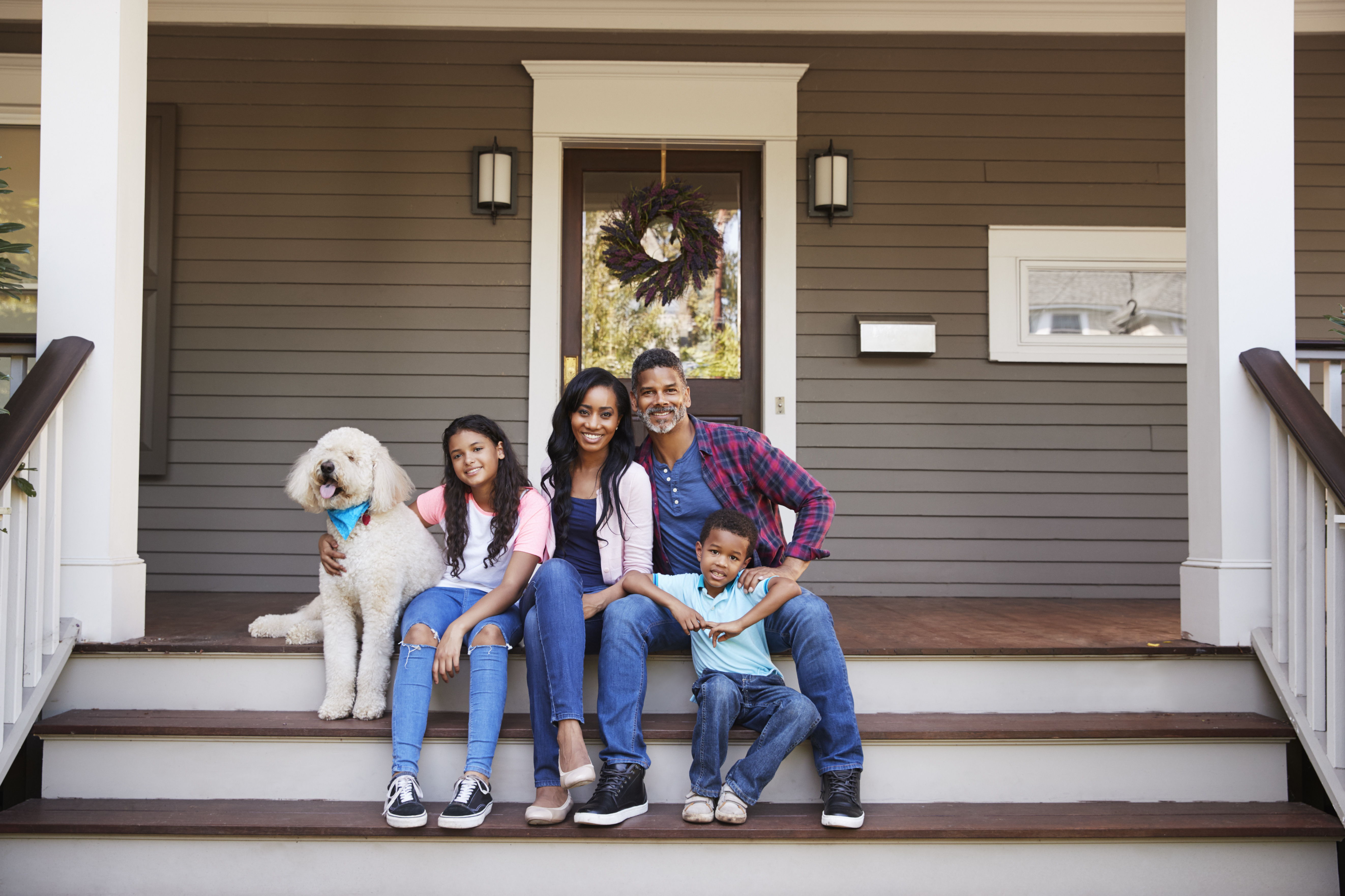 family of four sitting on the steps - cash out loan faqs