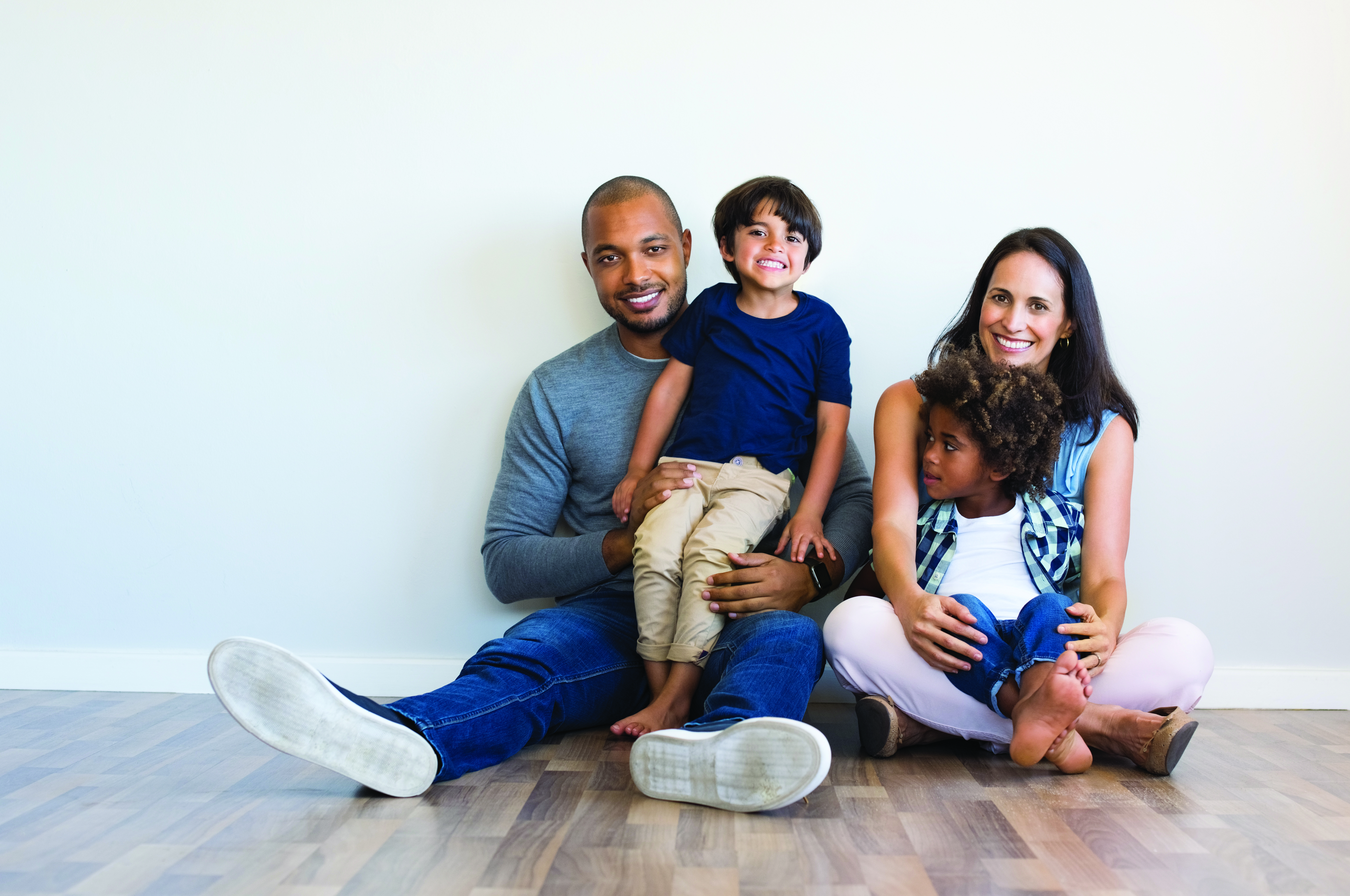 family of four sitting on the floor - types of home loans