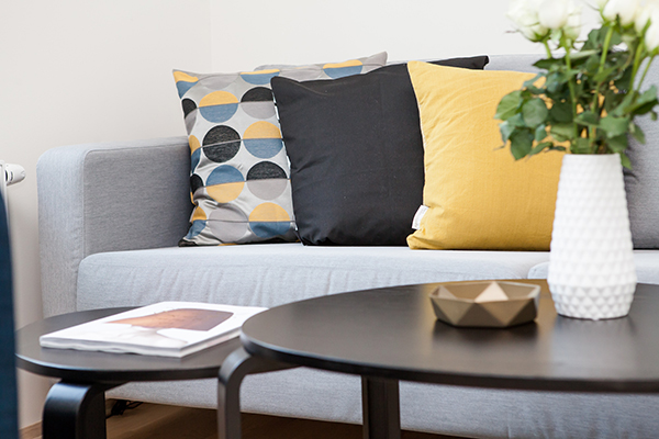 Grey Sofa with Blue and Yellow Pillows, Stylish Coffee Table