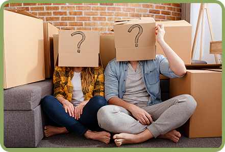 Couple sitting amongst moving boxes. Boxes have question marks.