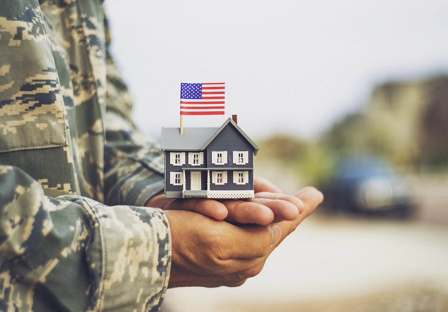 Military Person Holding a model home with a flag