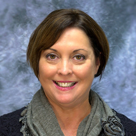 Professional headshot of Jody Brooking wearing a grey scarf