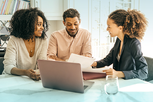 Man and woman looking at mortgage documents with loan officer