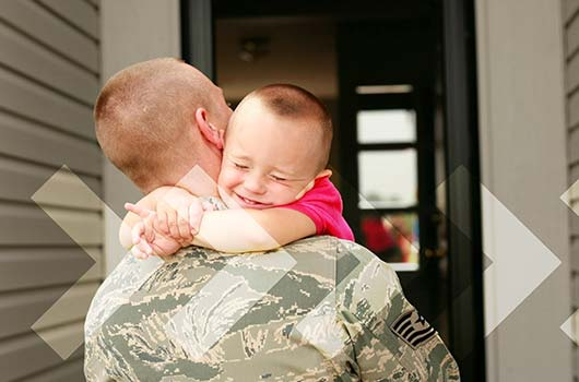 VA Home Loan - A soldier hugging his son as he returns home.