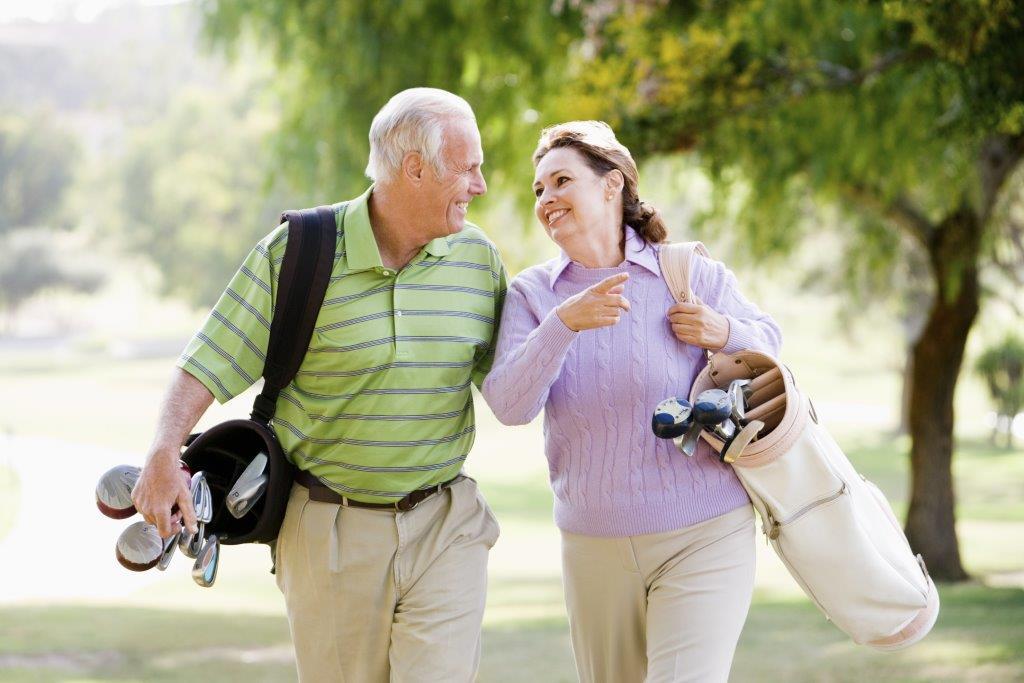 Elderly couple golfing