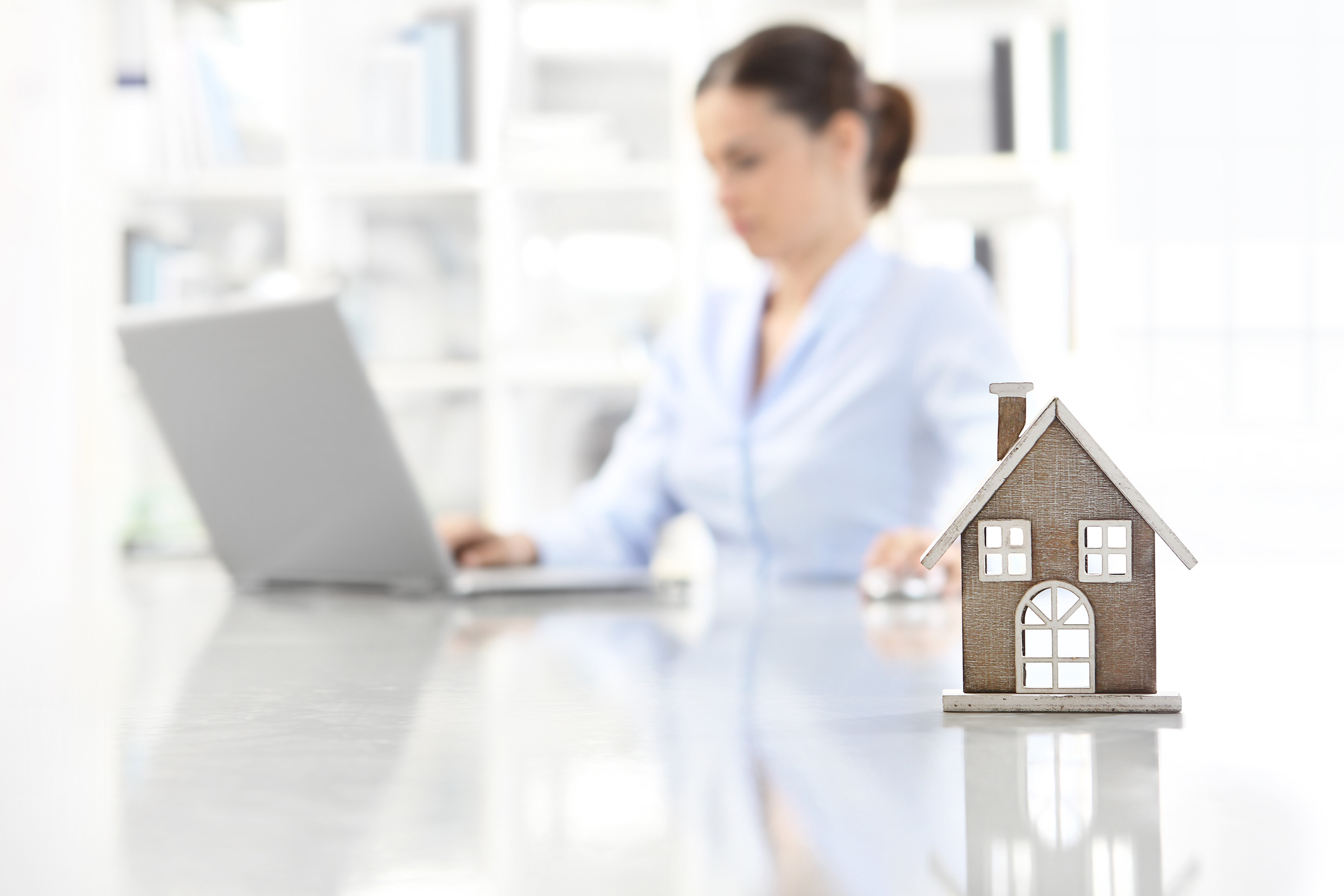 Woman on a computer and a house image