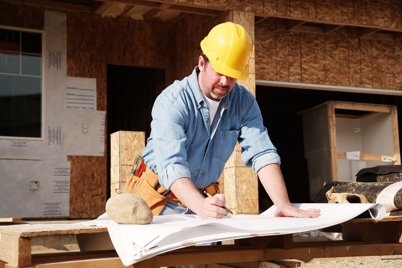 Man, blueprints, new construction house