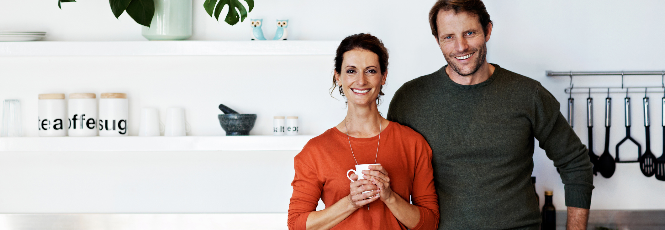 Couple standing in kitchen smiling
