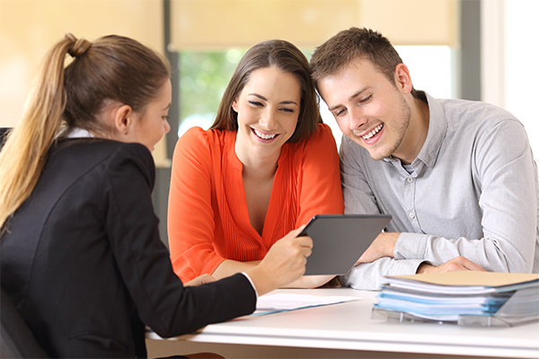 A young couple looking at an iPad with their mortgage originator